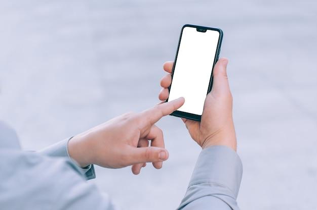 Makieta biznesmen trzyma w rękach smartfona