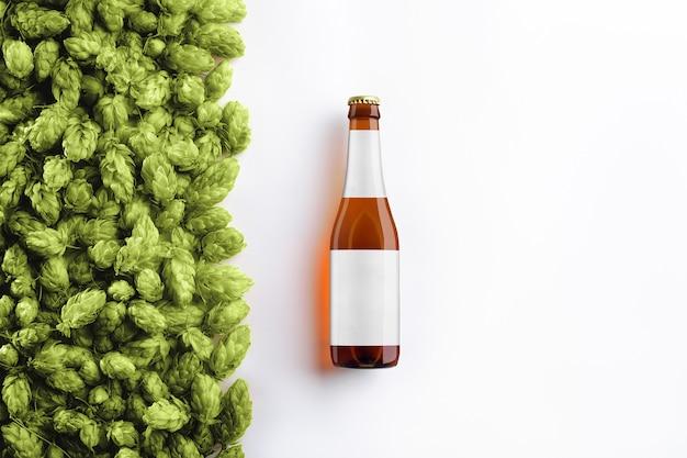 Makieta butelki piwa brązowy na białym tle z szyszek chmielowych i realistyczne cienie i odbicia. na szkle znajduje się szara etykieta. widok z góry. szablon gotowy do projektu.