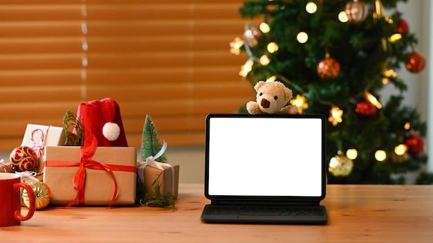 Makieta cyfrowego tabletu i prezenty świąteczne na drewnianym stole w salonie.