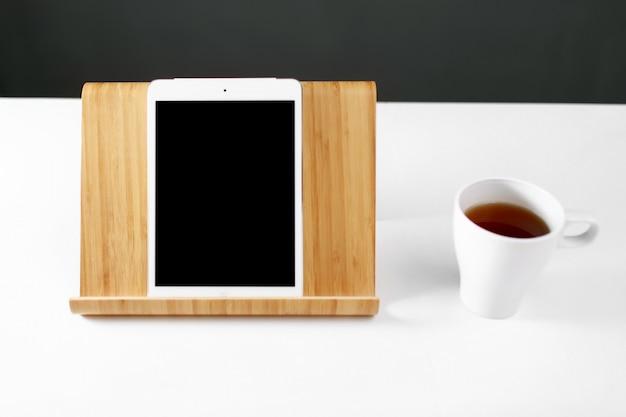Makieta cyfrowy tablet na drewnianym stojaku. tablet na drewnianym stojaku. biały kubek z herbatą. biuro pracy