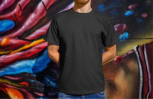 Makieta czarna męska koszulka na młodym chłopaku na tle ściany z graffiti, widok z przodu. szablon odzieży casual do prezentacji designu i reklamy w sklepie internetowym.