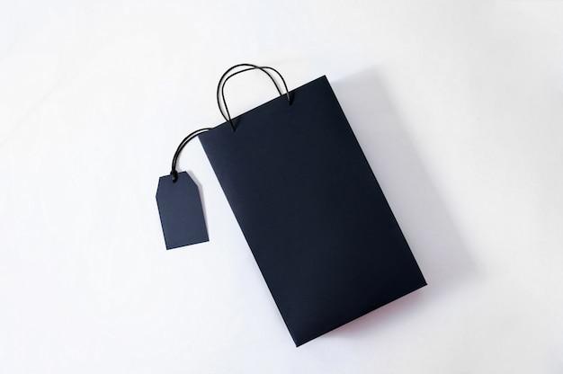 Makieta czarna papierowa torba na białym tle. sprzedaż koncepcyjna.