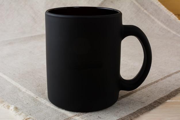 Makieta czarnego kubka do kawy na lnianej serwetce