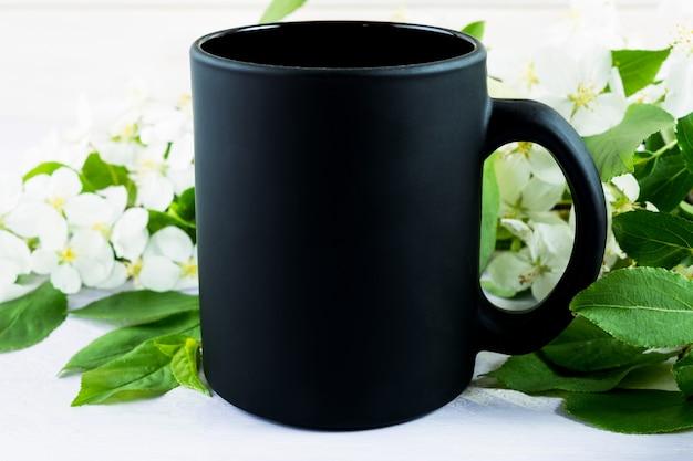 Makieta czarnego kubka do kawy z kwiatem jabłka