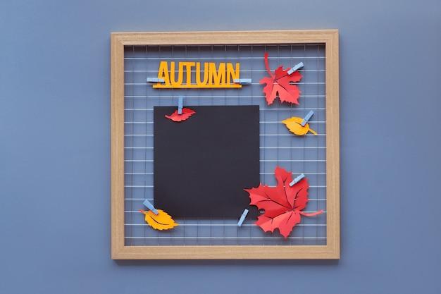 """Makieta czarnego papieru na twój napis, kaligrafię lub zdjęcie. tablica fotograficzna z szkarłatnym czerwonym szkłem i żółtym papierem w kolorze szafranowym. jesienne liście i napis """"jesień"""" na kołkach."""