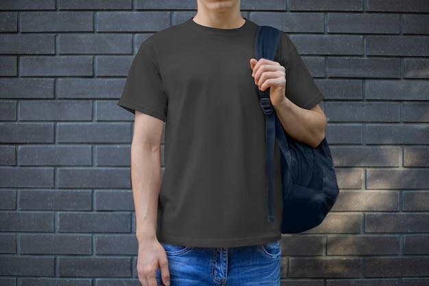 Makieta czarnej koszulki męskiej na młodym chłopaku przy ścianie z cegły, widok z przodu. szablon odzieży casual do prezentacji designu i reklamy w sklepie internetowym.