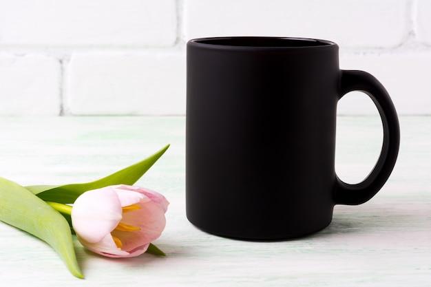 Makieta czarny kubek kawy z różowym tulipanem