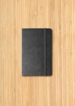 Makieta czarny notatnik zamknięty na białym tle na drewniane