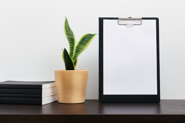 Makieta czarny schowka z kaktusem w garnku i książki na ciemnym stole roboczym i białym tle