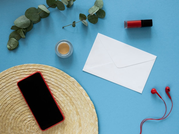 Makieta czerwonego kobiecego ekranu smartfona. płasko leżące czerwone słuchawki, kosmetyki i koperta. koncepcja aplikacji poczty, wiadomości i czatu.