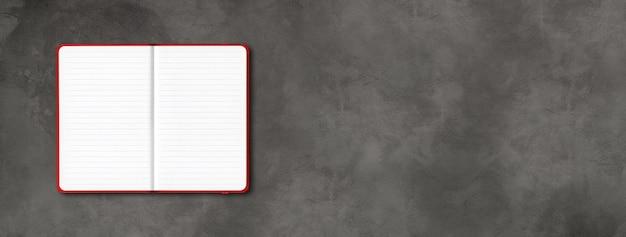 Makieta czerwony notatnik otwarty na białym tle na ciemnym betonie