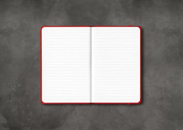 Makieta czerwony otwarty notatnik w linie na białym tle na ciemnym tle betonu