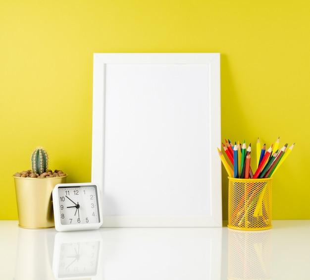 Makieta czysta biała ramka, kolorowe kredki na jasnym żółtym tle