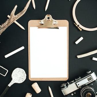 Makieta do schowka z kozimi rogami, aparatem retro, ręcznie robioną łyżeczką, ołówkami i akcesoriami na czarnej tablicy kredowej