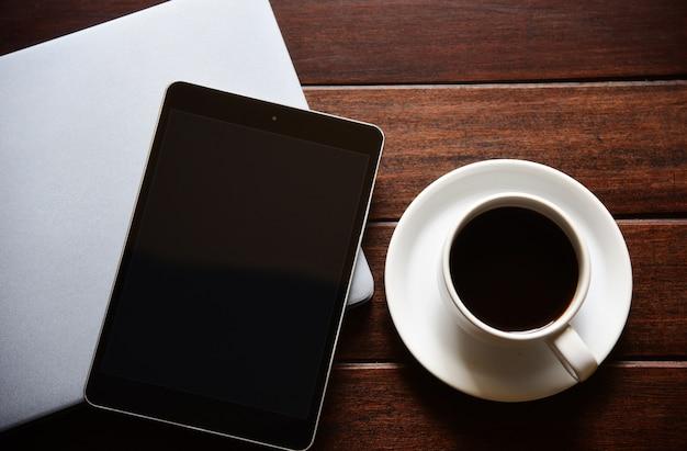 Makieta do tabletu pusty ekran i filiżanka kawy na biurku w biurze w domu w domu