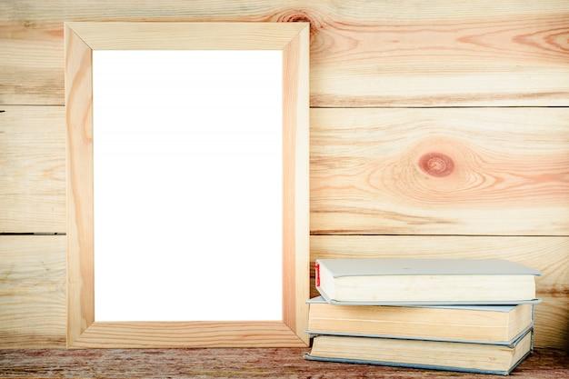 Makieta drewniana rama i stare książki na drewnianym tle