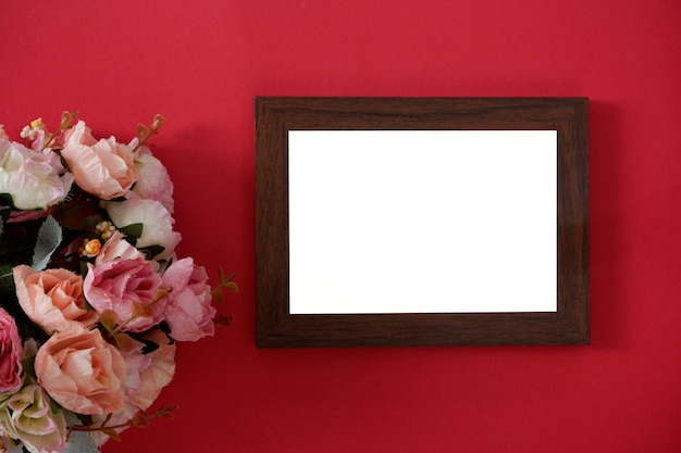 Makieta drewniana ramka na zdjęcia z miejsca na tekst lub obraz na czerwonym tle i kwiat.