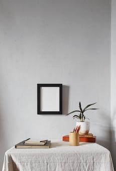 Makieta drewnianej ramy. skandynawski minimalistyczny design. doniczka na stosie książek na starym drewnianym biurku. kompozycja na białej powierzchni ściany