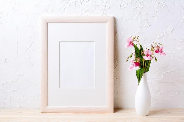 Makieta drewnianej ramy z fioletowymi kwiatami w eleganckim wazonie
