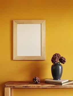 Makieta drewnianych ramek. susz ozdobne karczochy w wazonie na starej drewnianej półce. skład na żółtej powierzchni ściany