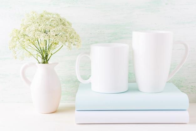 Makieta dwa białe kubki z książkami i białe kwiaty w dzban