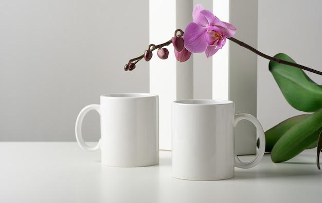 Makieta dwóch białych kubków na stole z dekoracją w kwiaty orchidei w minimalistycznym wnętrzu.