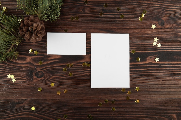 Makieta dwóch kartek świątecznych z gałązkami jodły i złotymi gwiazdami na vintage drewnianym.