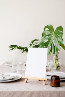 Makieta etykiety pustej ramki menu w restauracji barowej, stojak na broszury z białym papierem, drewniana karta namiotu na stole restauracyjnym z tropikalnym bukietem
