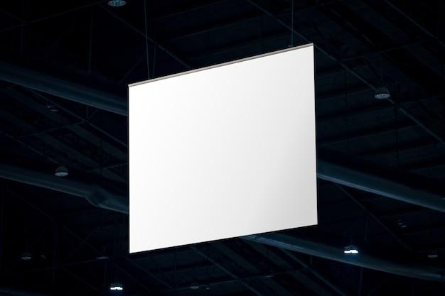 Makieta i pusty biały ekranowy billboard na reklamy lub informacje wiszące w sali konferencyjno-wystawienniczej.