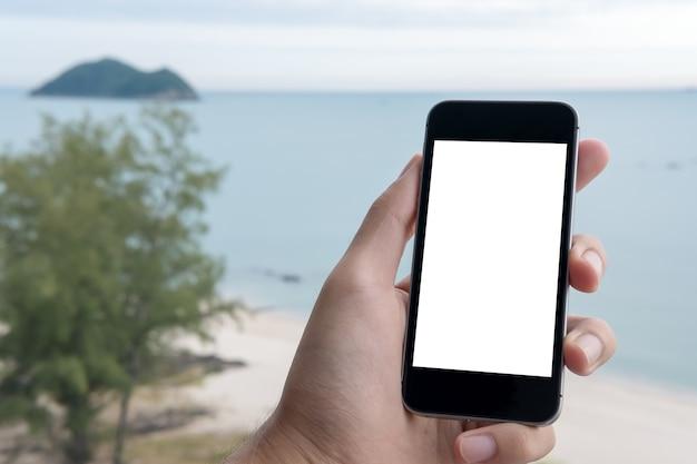 Makieta inteligentny telefon z ręki ludzi nad morzem