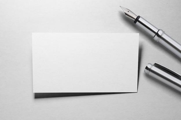 Makieta jednej wizytówki z wiecznym piórem na powierzchni białego papieru z teksturą