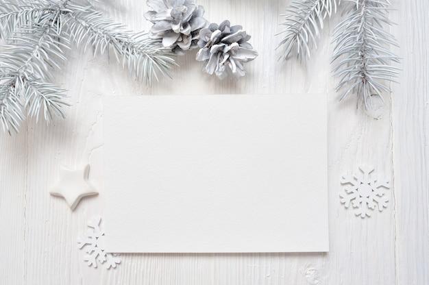Makieta kartki świąteczne pozdrowienia z białym drzewem i stożkiem, flatlay