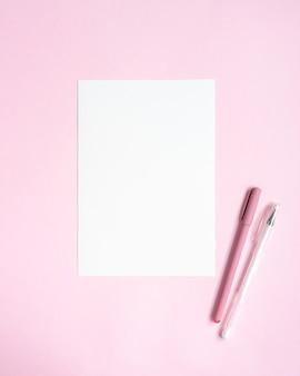 Makieta karty a5 z białym zaproszeniem z dwoma długopisami na różowym stole.
