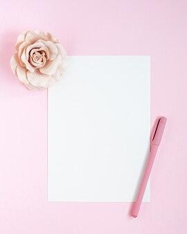 Makieta karty a5 z białym zaproszeniem z jednym piórem i kwiatem róży na różowym stole.