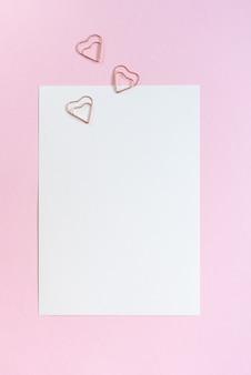 Makieta karty a5 z białym zaproszeniem z trzema klipsami w kształcie serca na różowym stole.