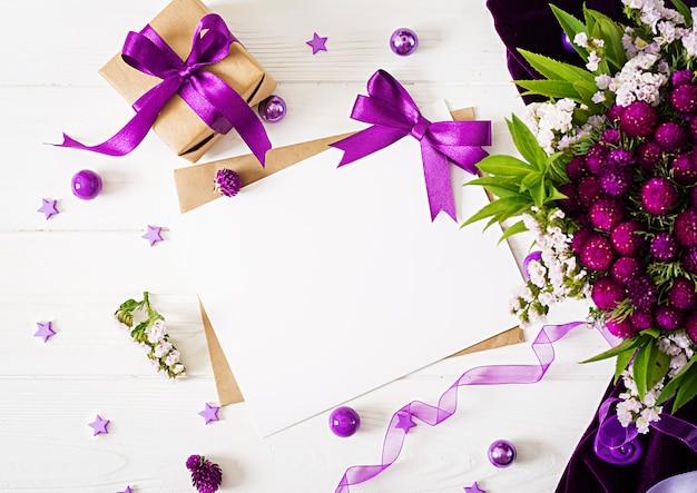 Makieta. karty i kwiaty, prezent pudełko, fioletowe wstążki i tkaniny leżące na białym stole.