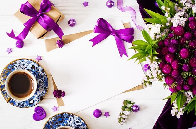 Makieta. karty i kwiaty, pudełko prezent, fioletowa wstążka, poranna kawa kubek i tkaniny leżące