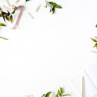 Makieta kobiecego biura domowego z gałęziami, złotym długopisem, klipsami i beżową wstążką