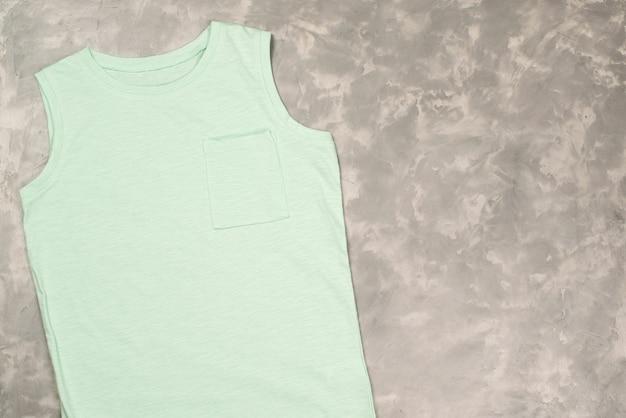 Makieta kolorowej koszulki, widok z góry. t-shirt na betonowym szarym stole, miejsce na kopię.
