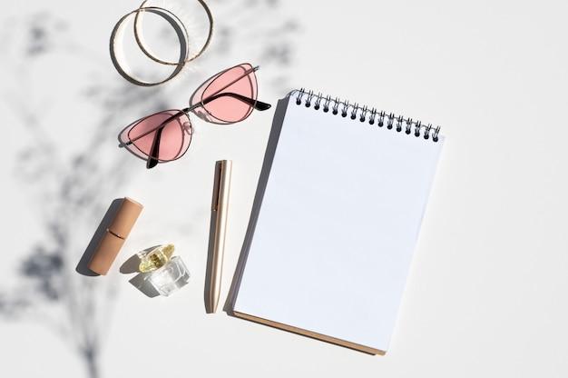 Makieta koncepcja miejsca pracy kobiety. kobiece dodatki ze spiralnym notesem i cieniem z gałęzi kwiatka. makieta modnych cieni z widokiem z góry z miejscem na kopię