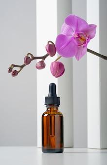 Makieta kosmetycznego serum do twarzy w brązowej szklanej butelce z pipetką na stylowym minimalistycznym białym tle z geometrycznym wystrojem i kwiatami orchidei.