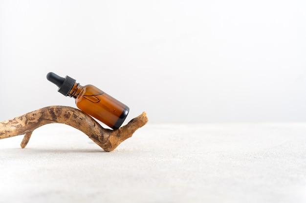 Makieta kosmetycznego serum do twarzy w brązowej szklanej butelce z pipetką na stylowym minimalistycznym białym tle z korą drzewa