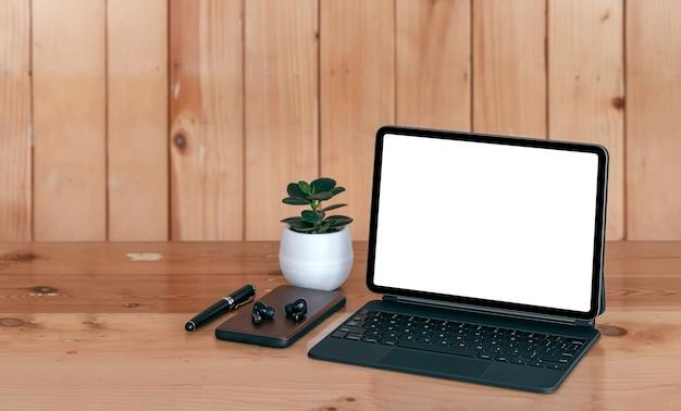 Makieta kreatywnego obszaru roboczego w stylu vintage z pustym ekranem i magiczną klawiaturą, smartfonem, słuchawkami i długopisem na drewnianym stole z desek.