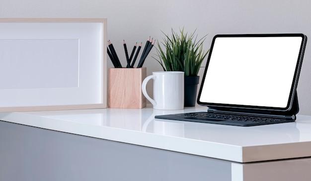 Makieta kreatywnego obszaru roboczego z tabletem z pustym ekranem i magiczną klawiaturą na białym stole w nowoczesnym pokoju.