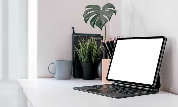 Makieta kreatywnego obszaru roboczego z tabletem z pustym ekranem na białym blacie w nowoczesnym pokoju.