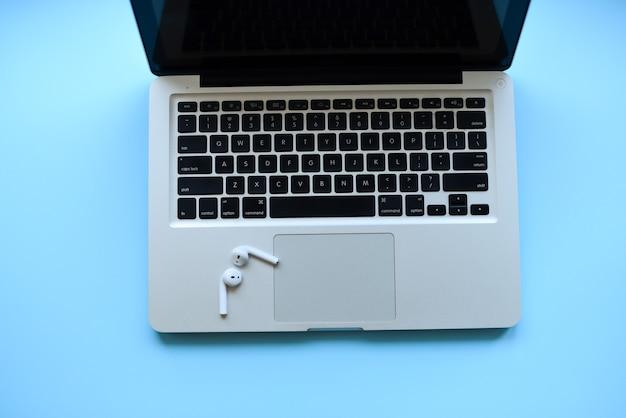 Makieta . laptop i air pods na niebieskim stole z klawiaturą