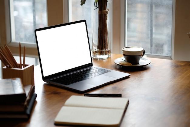 Makieta laptop na drewnianym stole.