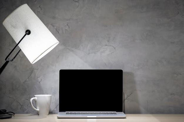Makieta laptop z lampą stołową i biały kubek na drewno
