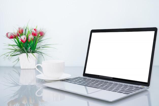 Makieta laptopa i filiżanka kawy z kwiatem
