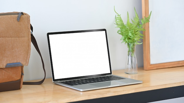 Makieta laptopa, torby, białej tablicy i dekoracji roślin na drewnianym stole.